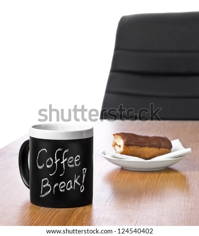 office desk with mug of coffee with coffee break text in chalk