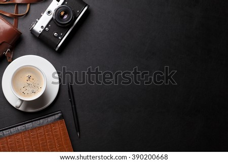 Office desk with photo camera, coffee and notepad. Top view with copy space