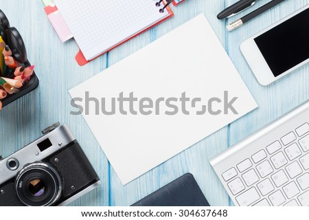 Office desk with supplies, camera and blank card. Top view with copy space