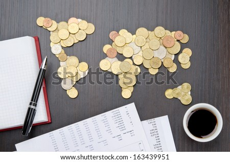 Office desk with world map made of money coins and agenda
