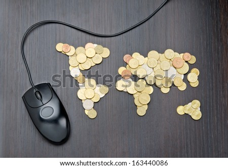 Office desk with world map made of money coins and computer mouse