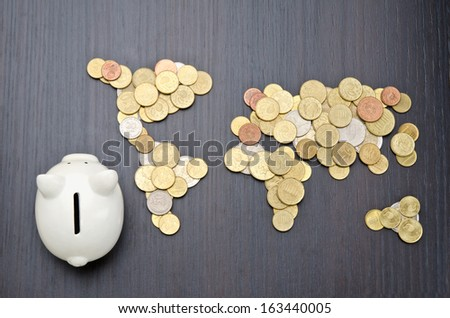 Office desk with world map made of money coins and piggy bank