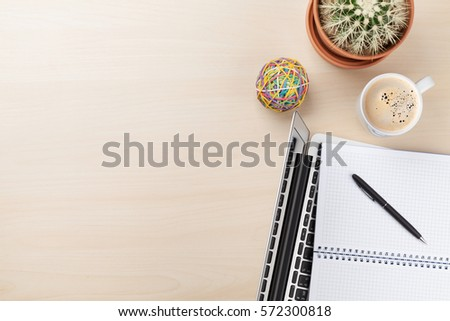 Office desk workplace with laptop, coffee and cactus on wooden background. Top view with copy space