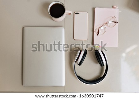 Office desk workspace from top view above flat lay objects. Modern minimal design desktop for creative working with laptop, coffee, smartphone, headphones. Minimalism concept.