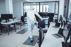 Office disinfection during COVID-19 pandemic. Man in protective suit and face mask spraying for disinfection in the office