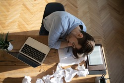 Office employee sleeping at workplace desk, above view. Desperate worker not find solution or creative ideas got tired, fell asleep, heap of crumpled papers on table. Chronic fatigue syndrome concept