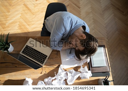 Office employee sleeping at workplace desk, above view. Desperate worker not find solution or creative ideas got tired, fell asleep, heap of crumpled papers on table. Chronic fatigue syndrome concept Foto stock ©