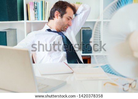 Office employee sweating and smelling and notices his sweat under armpit #1420378358