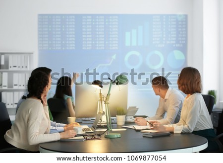 Office employees watching presentation during meeting. Forex concept