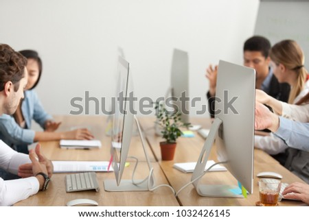 Office employees working on pc computers talking sharing desk in co-working, diverse business people using desktops sitting together, team workplace, teamwork concept, close up of table with monitors #1032426145