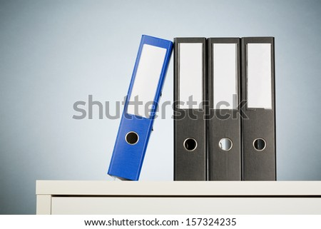 Office folders on a white desk with a light blue background.