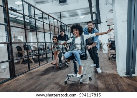 Office fun. Four young cheerful business people in smart casual wear having fun while racing on office chairs and smiling