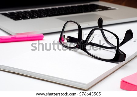 Office items are on a table: laptop, notebook, glasses. Blogging. Workplace close up photo #576645505