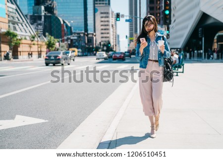 office lady waiting her boyfriend to pick her up beside the road after work. Business woman in motion, calling on mobile smart phone walking outside in city centre. young asian worker lifestyle. stock photo
