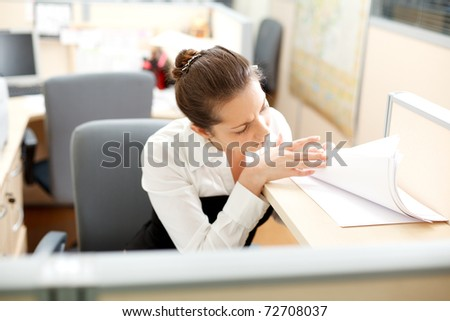 Office life. Woman searches for documents at the table.