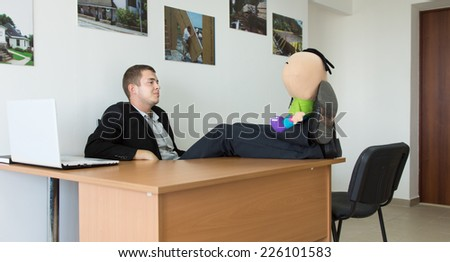 Office Man Taking a Break at His Work Area, Putting His Feet on the Table with Stuffed Toy.