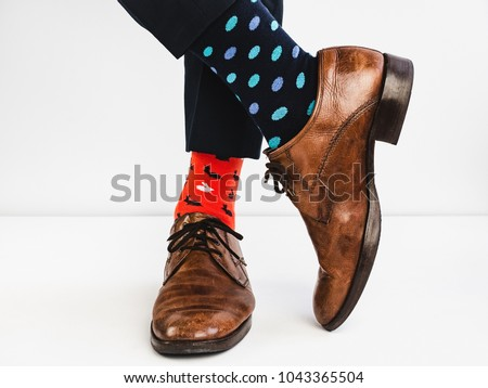 Office Manager in stylish shoes, blue pants and bright, colorful socks on a white background. Lifestyle, fashion, fun