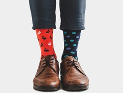 Office Manager in stylish shoes, blue pants and bright, colorful socks on a white, isolated background. Close-up. Style, fashion, fun, elegance