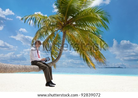Office manager with tablet pc sitting on palm tree on the Maldivian beach and looking at camera smiling
