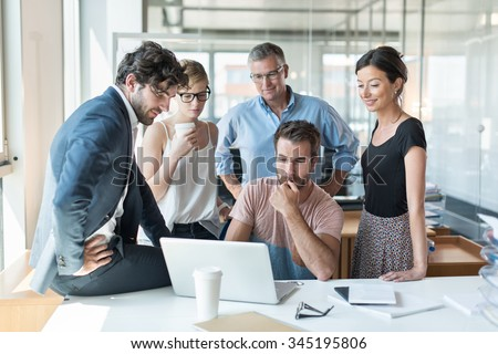 Office meeting, everybody is looking at the computer engineer website presentation. He is sitting at a desk in a luminous open space, the team is standing around him with the grey hair senior partner