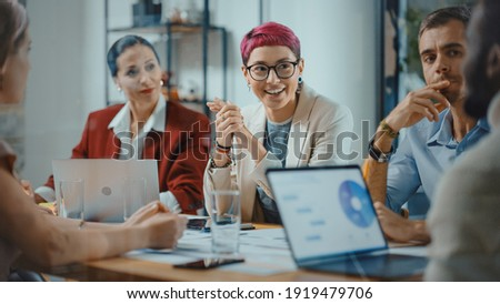 Office Meeting in Conference Room: Beautiful Specialist with Short Pink Hair Talks about Firm Strategy with Diverse Team of Professional Businesspeople. Creative Start-up Team Discusses Big Project