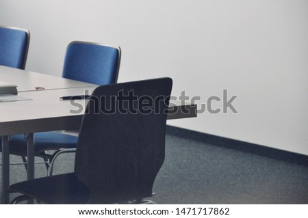 Office monotony symbolized by an empty meeting room with a table and chairs and an undecorated wall