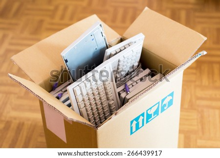 Office move concept - cardboard box with lots of computer keyboards on the wooden floor
