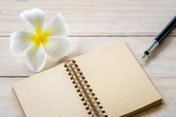 Office nature work, Blank notebook with pen and plumeria flower on wooden table background.