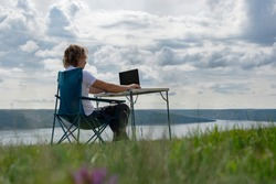 Office outdoors. Guy works at the remote work enjoying beautiful nature. River bank and dense green grass