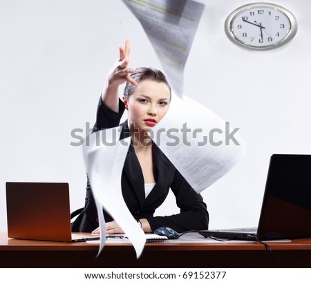 office portrait of beautiful dissatisfied business woman with two laptops angrily throwing documents to the camera