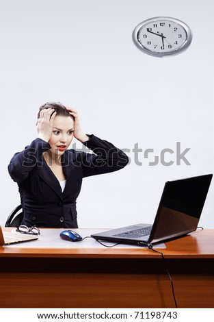 office portrait of beautiful shocked business woman sitting at her workplace with two laptops on gray