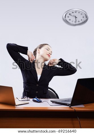 office portrait of beautiful tired business woman stretching at her workplace with two laptops on gray