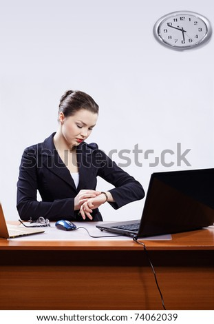 office portrait of beautiful young business woman sitting at her workplace with two laptops on gray and regulating her watches