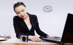 office portrait of beautiful young woman inserting usb wire of compact digital camera into laptop header