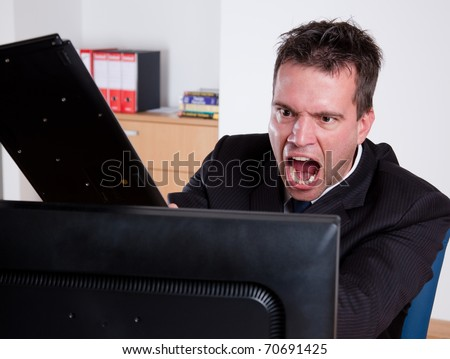 Office rage series. Businessman slamming keyboard on the monitor.