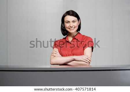 Office receptionist in a red blouse, smiling