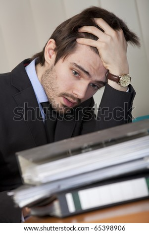 office scene - frustrated and overworked man with many folders