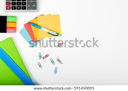 office, school, business, education and technology concept - close up of notebook, paper stickers, pencil, clip, calculator, different stuff on white background