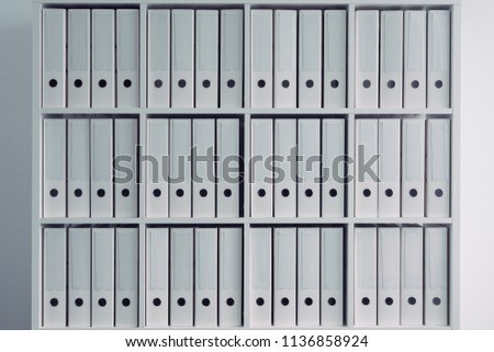 Office shelf with file ring binder folders in white color for archive and data organization concepts