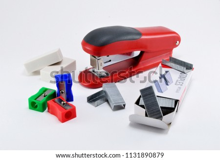Office stapler and stapler staples, erasers and sharpeners on white background.