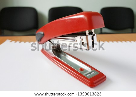 Office stapler. Red stapler for office paper on a background of black chairs