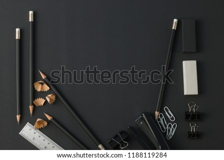 Office stationery top view. workspace with pencils, ruler, eraser, paper clip, stapler, on black desk flat lay.