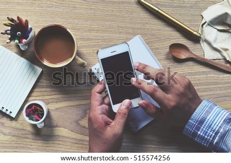 Office stuff and it gadgets display on top view business desk with copy space at text of picture. Creative table, modern project. Business man is hand working smartphone. Dark tone filter effects.  #515574256