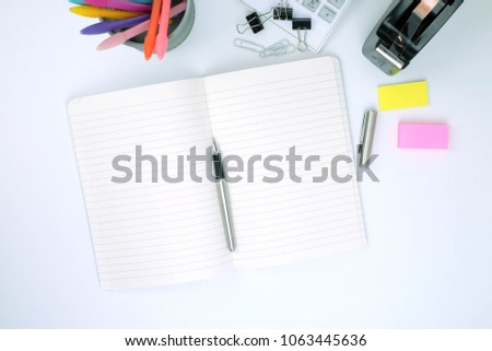 Office supplies and stationery include a calculator, notebook, punch, stapler, paper clips, post it note and Various colour pen in cup on white desk background.