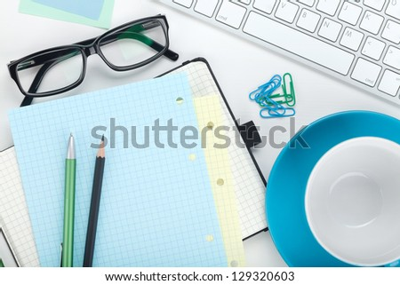 Office supplies, computer keyboard and coffee cup. View from above. On white background
