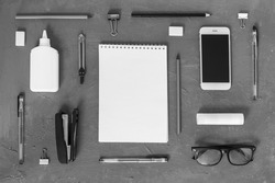 Office supplies.Everything for school and office. Notepad, pens, pencils, notepads,telephone, stapler and everything you need on a gray concrete background.Everything is black and white.Flatly. mock