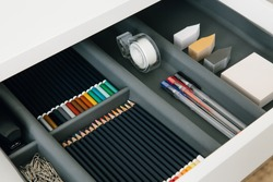Office supplies in desktop drawer. Writing pens, pencils, paper clips, color sheets for notes. Workplace order.