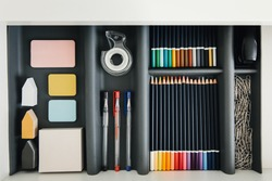 Office supplies in desktop drawer. Writing pens, pencils, paper clips, color sheets for notes. Workplace order. Student desk.