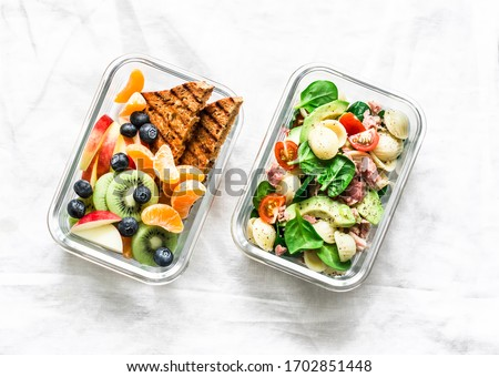 Office sweet and savory food lunch box. Pasta, tuna, spinach, avocado salad and fruit, peanut butter sandwiches lunch box on light background top view