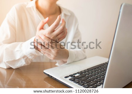 Office syndrome - Young female suffering from hand pain while using laptop at workplace. Occupational risk factor for carpal tunnel syndrome or trigger finger. Health care and medical concept. #1120028726